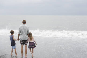 Back view of man standing hand in hand with little daughter and son at seafront - EYAF00720