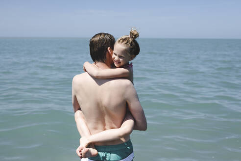 Father carrying his little daughter at the sea - EYAF00723