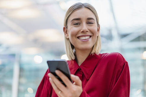 Portrait of a smiling young businesswoman with cell phone - DIGF08981