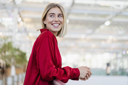 Portrait of a happy young businesswoman standing at a railing - DIGF08990