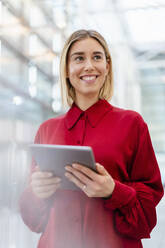 Smiling young businesswoman wearing red shirt using tablet - DIGF09008