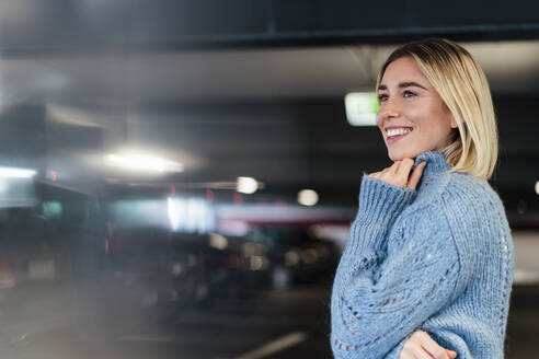Portrait of a smiling young woman in a parking garage - DIGF09017