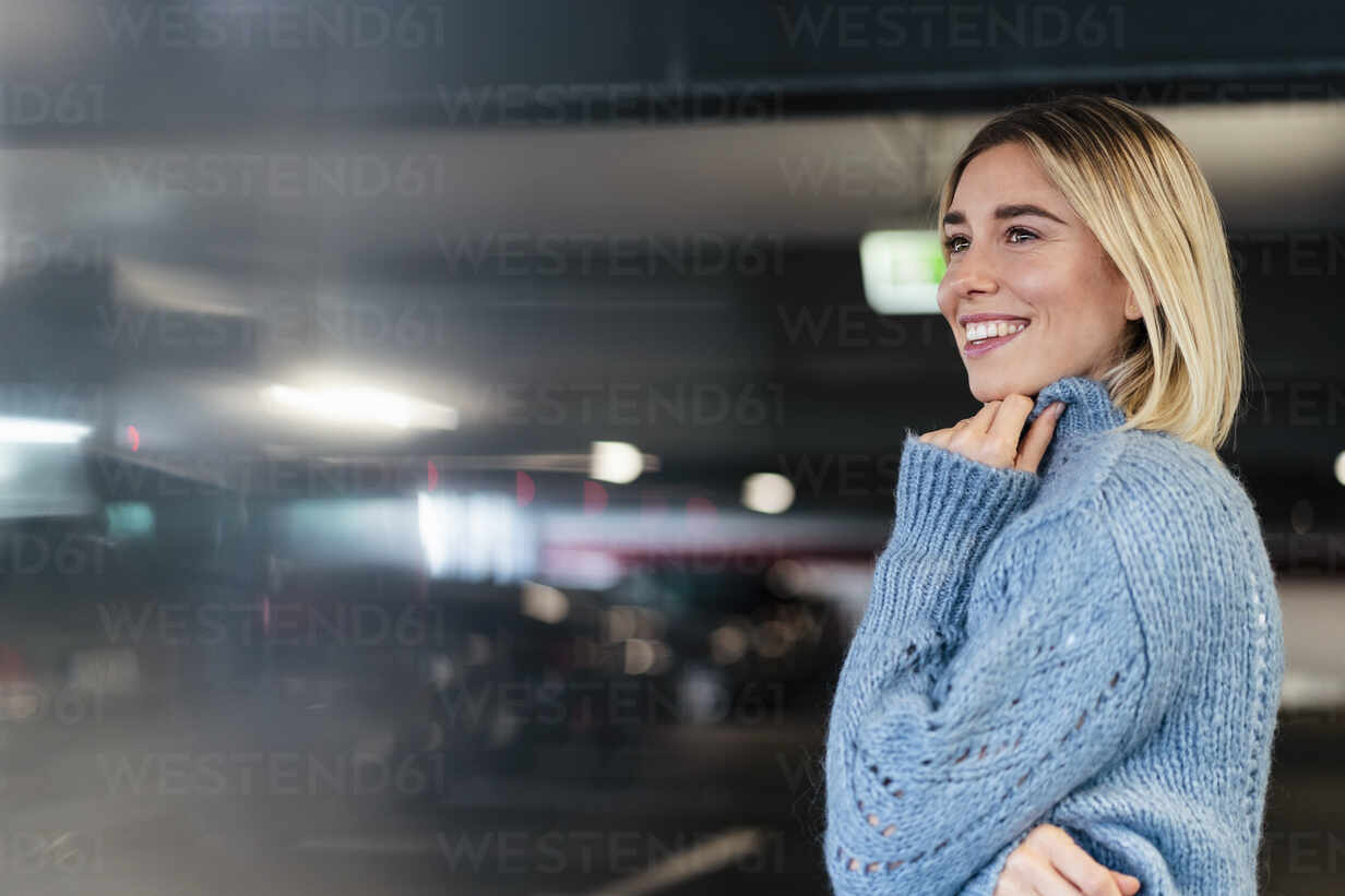 Portrait of a smiling young woman in a parking garage - DIGF09017 - Daniel Ingold/Westend61