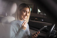 Happy young woman with tablet and earphones in a car - DIGF09023