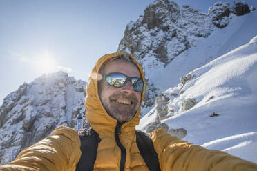 Selfie of a happy mountaineer on snowy mountain, Lecco, Italy - MCVF00086