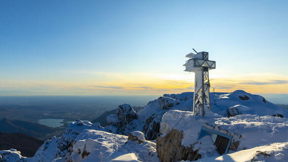 View over snowy mountains with a frozen summit cross, Lecco, Italy - MCVF00092