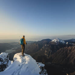 Mountaineer standing on top of a snowy mountain enjoying the view, Lecco, Italy - MCVF00095