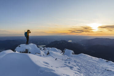 Mountaineer standing on top of a snowy mountain enjoying the view, Lecco, Italy - MCVF00101