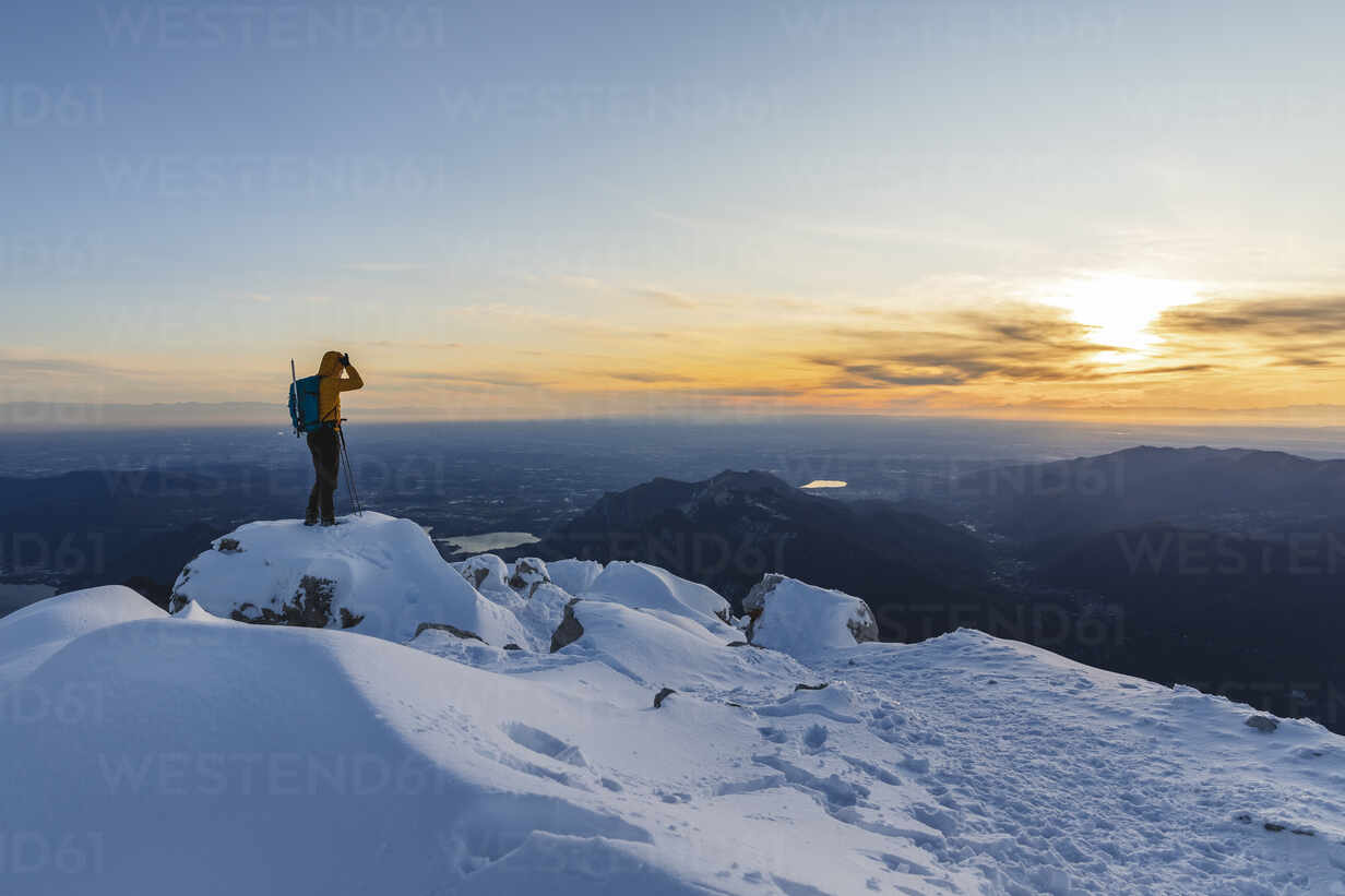 Mountaineer standing on top of a snowy mountain enjoying the view, Lecco, Italy - MCVF00101 - 27exp/Westend61