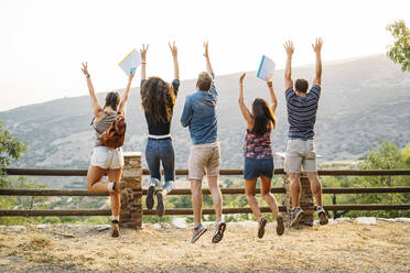 Rear view of happy friends jumping in rural landscape - MPPF00347