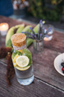 Detox water with  lemon and peppermint on table - MPPF00362