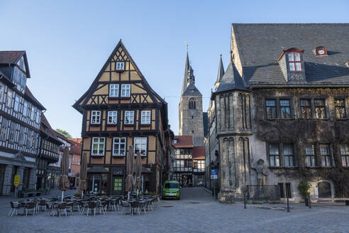 Germany, Saxony-Anhalt, Quedlinburg, Chairs in front of half-timbered cafe in historical town - RUNF03473