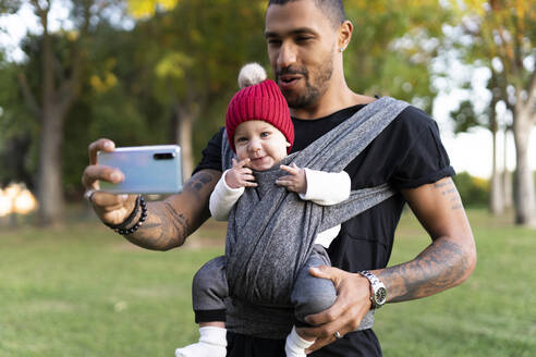 Young father carrying baby son in a baby sling, taking smartphone selfie - ERRF02213