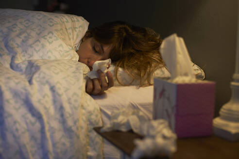 Sick woman using tissues in the bed - VEGF00994