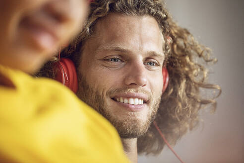 Portrait of smiling young man listening to music with woman in foreground - MCF00390
