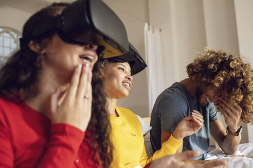 Happy friends having fun with VR glasses in bed at home - MCF00393