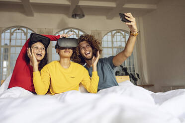 Happy friends having fun with VR glasses and smartphone in bed at home - MCF00396