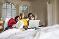 Friends relaxing in bed at home watching a movie on laptop - MCF00399