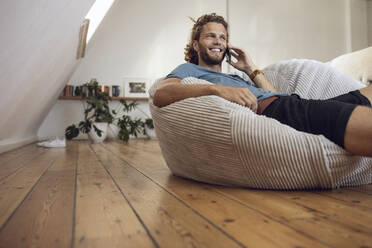 Smiling young man relaxing in beanbag at home talking on the phone - MCF00402