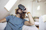 Young man wearing VR glasses at home - MCF00405