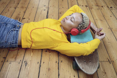Young woman lying on skateboard on the floor at home listening to music - MCF00411