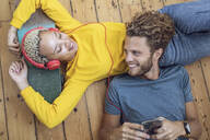 Happy young couple lying on the floor at home relaxing - MCF00414