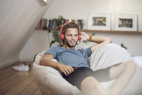 Young man relaxing in beanbag at home listening to music - MCF00417