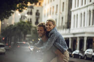 Happy young man carrying girlfriend piggyback in the city - MCF00426