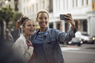 Two carefree young women taking a selfie in the city - MCF00429
