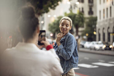 Young woman posing for a smartphone picture in the city - MCF00432