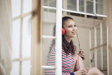 Happy young woman at the window listening to music - MCF00441