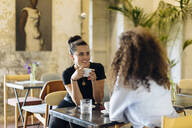 two girlfriends meeting and talking in a bistro - SODF00414