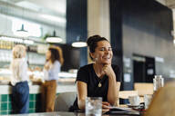 Young woman sitting in bistro, laughing - SODF00417