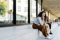 Women sitting on steps in the city - SODF00429