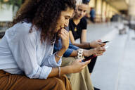 Three women sitting on steps in a row, using smartphones - SODF00432