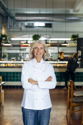 Proud business owner standing in her bistro with arms crossed - SODF00438
