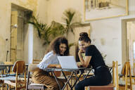 Friends working together in a bistro, using laptop - SODF00441
