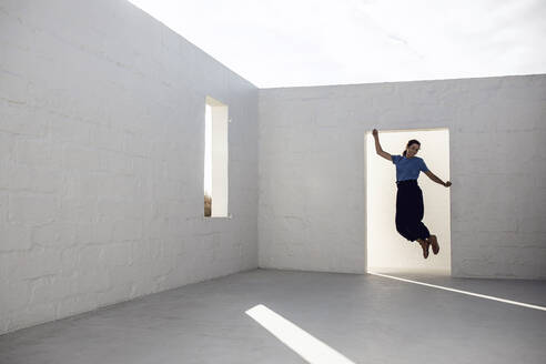 Businesswoman jumping for joy in empty room - MCF00446