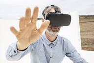 Mature man wearing VR goggles - MCF00455