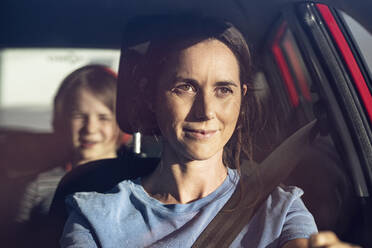 Young woman driving car with seat belt, daughter in backseat - MCF00473