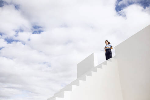 Businesswoman standing on white stairs, using smartphone - MCF00476