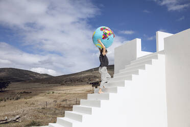Little girl on white stairs, carrying inflatable globe - MCF00485