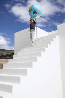 Little girl on white stairs, carrying inflatable globe - MCF00488