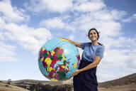 Mature woman holding inflatable globe, looking confident - MCF00491