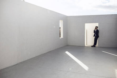 Businessman leaning in door frame of empty space, talking on the phone - MCF00500