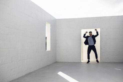 Businessman cheering and dancing with raised arms in empty room - MCF00503