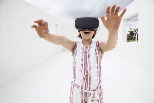 Little girl discovering empty space with VR goggles - MCF00515