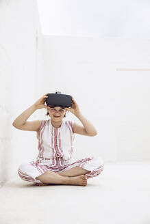 Girl with VR goggles sitting on ground of empty space - MCF00518