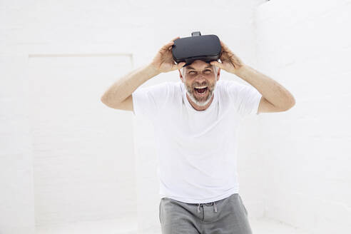 Mature man with VR goggles, looking at camera, laughing - MCF00521