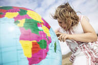 Little girl pointing on inflatable globe - MCF00524